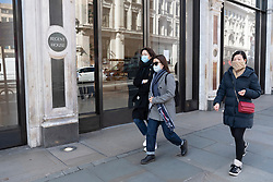 © Licensed to London News Pictures. 16/03/2020. London, UK. People wearing masks walk past a closed Apple flagship store in Regent Street as the Coronavirus outbreak affecting businesses and tourism in London. Photo credit: Ray Tang/LNP
