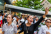 28 APRIL 2014 - BANGKOK, THAILAND: Mourners, including a woman holding one his books, cry out during the funeral for Kamol Duangphasuk, 45, in Bangkok. Kamol was a popular poet who wrote under the pen name Mai Nueng Kor Kunthee. Kamol had been writing since the 1980s and was an outspoken critic of the 2006 coup that deposed Thaksin Shinawatra. After the 2010 military crackdown against the Red Shirts he went into temporary self imposed exile fearing for his safety. After he returned to Thailand he organized weekly protests against Thailand's Lese Majeste laws, which he said were being used to stifle dissent. Kamol was shot and murdered on April 23. The assailants are still at large but the murder is thought to be political.     PHOTO BY JACK KURTZ