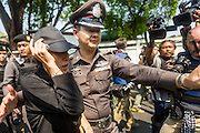 """01 FEBRUARY 2014 - BANGKOK, THAILAND: A Thai police officer helps an anti-government worker get away from a mob of voters upset that they couldn't vote because she and other protestors blocked access to the polls. Thais went to the polls in a """"snap election"""" Sunday called in December after Prime Minister Yingluck Shinawatra dissolved the parliament in the face of large anti-government protests in Bangkok. The anti-government opposition, led by the People's Democratic Reform Committee (PDRC), called for a boycott of the election and threatened to disrupt voting. Many polling places in Bangkok were closed by protestors who blocked access to the polls or distribution of ballots. The result of the election are likely to be contested in the Thai Constitutional Court and may be invalidated because there won't be quorum in the Thai parliament.    PHOTO BY JACK KURTZ"""