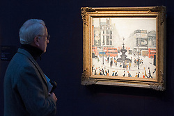 """© Licensed to London News Pictures. 21/03/2014. London, UK. A visitor to Sotheby's auction house views """"Piccadilly Circus"""" (1959) (est. GB£2000,000-3,000,000) by British artist LS Lowry during the press view for a new sale of the artist's work in London today (21/03/2014). The auction, entitled """"Lowry: The AJ Thompson Collection"""", features works by Lowry assembled over a 30 year period by collector A.J. Thompson. Photo credit: Matt Cetti-Roberts/LNP"""