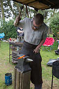 A man forging metal at a blacksmith display at the annual Suffolk Show on the 29th May 2019 in Ipswich in the United Kingdom. The Suffolk Show is an annual show that takes place in Trinity Park, Ipswich in the English county of Suffolk. It is organised by the Suffolk Agricultural Association.