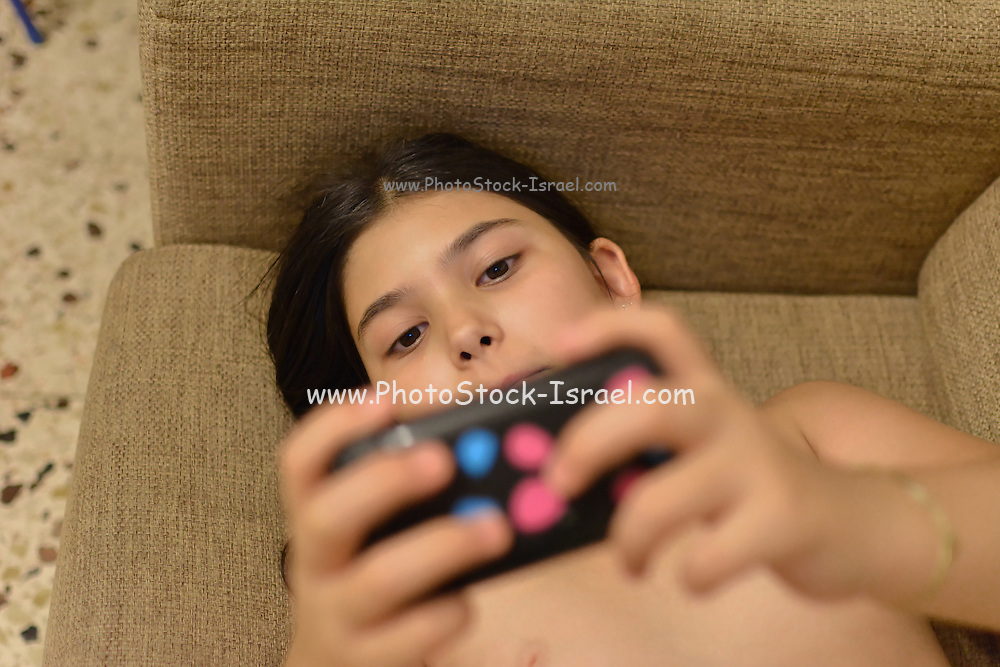 Young girl plays video games with a handheld game console Model released