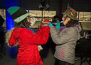 East Meadow, New York, USA. December 31, 2014. Two girls face each other blowing holiday horns at the New Year's Eve Party which started before the 5K New Year's Eve DASH to support the Long Island Council on Alcoholism and Drug Dependence (LICADD) at the Twin RInks Ice Center at Eisenhower Park in Long Island.