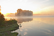 Early morning mist on the lake with reeds growing at the water's edge. Sunrise with reflections on the surface. Lake Flen, Smaland region. Sweden, Europe.