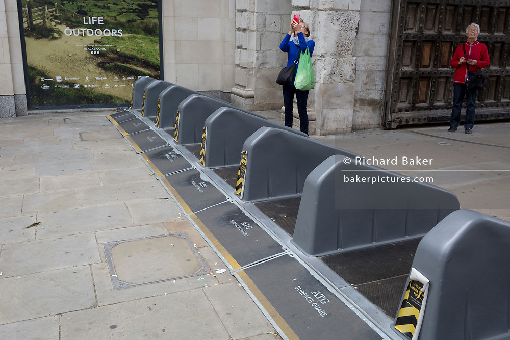 Pedestrians walk over security barriers at one of the entrances to Paternoster Square in the City of London - the capital's financial district, on 4th June 2018, in London, England.