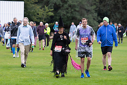 © Licensed to London News Pictures. 03/10/2021. London, UK. A runner wearing fancy dress arrives in Greenwich Park ahead of the start of the London Marathon.This London Marathon will be the first full scale staging of the race in more than two years due to the Coronavirus Pandemic.  Photo credit: George Cracknell Wright/LNP