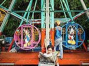 24 NOVEMBER 2015 - BANGKOK, THAILAND:  A woman reads a Thai newspaper while working the Ferris Wheel at the Wat Saket temple fair. Wat Saket is on a man-made hill in the historic section of Bangkok. The temple has golden spire that is 260 feet high which was the highest point in Bangkok for more than 100 years. The temple construction began in the 1800s in the reign of King Rama III and was completed in the reign of King Rama IV. The annual temple fair is held on the 12th lunar month, for nine days around the November full moon. During the fair a red cloth (reminiscent of a monk's robe) is placed around the Golden Mount while the temple grounds hosts Thai traditional theatre, food stalls and traditional shows.       PHOTO BY JACK KURTZ
