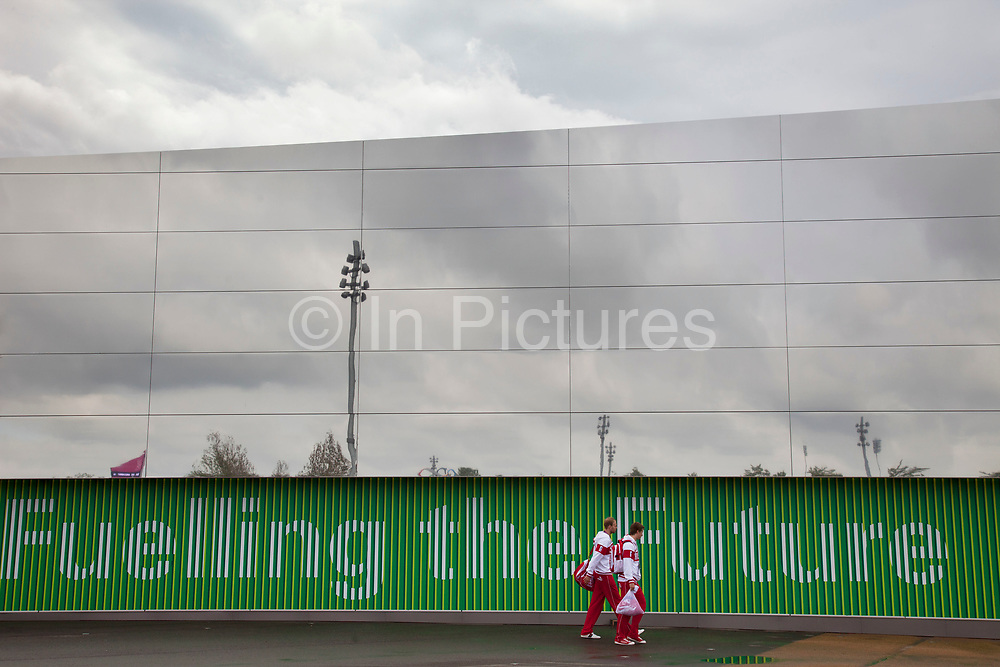 London 2012 Olympic Park in Stratford, East London. Two Russian basketball players walk past a large mirror covered building adorned with the words Fuelling the Future, owned by sponsor BP.