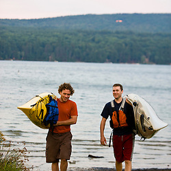 Two men carry their kayaks after paddling on Lake Sunapee at Mount Sunapee State Park in Newbury, New Hampshire.