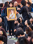 05 DECEMBER 2016 - BANGKOK, THAILAND:  A woman carries a portrait of the late King to a ceremony honoring His Majesty on Bhumibol Bridge. Tens of thousands of Thais gathered on Bhumibol Bridge in Bangkok Monday to mourn the death of Bhumibol Adulyadej, the Late King of Thailand. The King died on Oct 13 after a lengthy hospitalization. December 5 is his birthday and a national holiday in Thailand. The bridge is named after the late King, who authorized its construction. 999 Buddhist monks participated in a special merit making ceremony on the bridge.      PHOTO BY JACK KURTZ