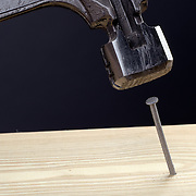 Hammering a nail into a pine board