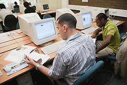 Man with hearing impairment with fellow students in university computer room.