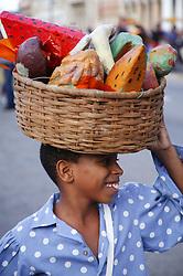 Boy carrying bowl of artificial fruit at Carnival; Havana; Cuba,