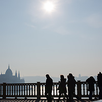 Tourists walk on a bridge in front of the Budapest cityscape seen from Margaret bridge in Budapest, Hungary on December 06, 2012. ATTILA VOLGYI