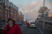 Pedestrians walk past buildings as water vapor and smoke rise from a Tonghua Iron & Steel Group Co. plant in the distance in the Erdaojiang district in Tonghua, Jilin province, China, on Wednesday, Jan. 6, 2016. The citys once-vaunted state-run steel mills have slipped inexorably into decline, weighed down by slumping global markets, a changing economy, and the burden of costs and responsibilities to the people of the town they fostered. Previous attempts to privatise the enterprise have met with stiff resistance, one such attempt resulted the mob lynching and death of a private businessman who wanted to invest and streamline the operation.