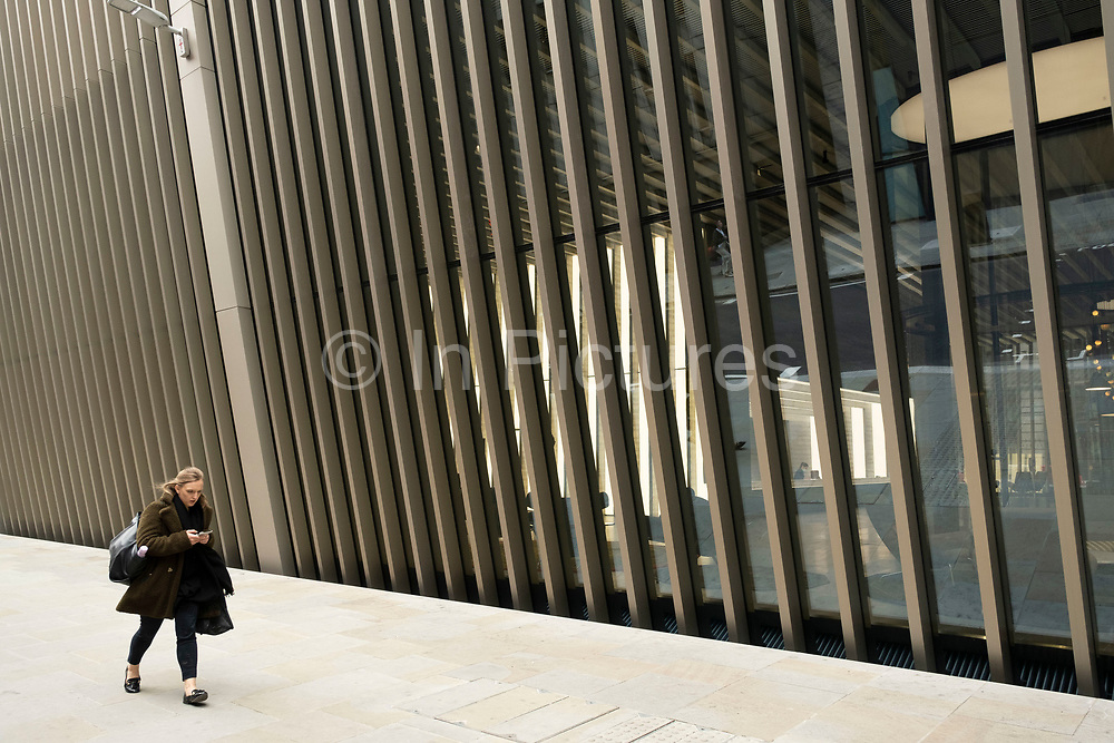 People interact with the modern architectural detailing on a wall outside a new office buiding in the City of London on 26th May 2021 in London, United Kingdom. As the coronavirus lockdown continues its process of easing restrictions, the City remains far quieter than usual, which asks the question if normal numbers of people and city workers will ever return to the Square Mile.