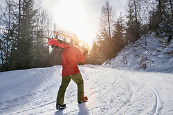 Man carrying his sledge uphill, Tyrol, Austria