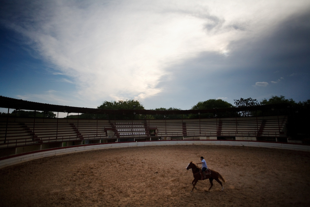 """Central Texas Charreria - Story Summary. The rodeo tradition called charreada began in 16th century Spanish colonial Mexico as a celebration that marked the close of a major cattle round-up. Teams of cowboys, called charros, competed against each other in events of horsemanship and roping skills.  ..The tradition continues today with more than 200 official charreada teams in the United States, 30 of those in Texas, preserving the technique and style of the historic Mexican charro.  Teams compete each weekend in different homemade arenas, called lienzos.  No cash prizes are awarded, just the respect of fellow charros...""""Keep the money, keep the belt buckle, we just want the bragging rights,"""" says Juan Gonzalez, President of the San Antonio Charro Association...----..A charro trains his horse in an empty lienzo in San Antonio, Texas.  Popular south of the border, charreada in Texas is a sparsely attended event with mostly family and other charro teams in attendance.  ..""""We're all amateurs,"""" says Juan Gonzalez, """"but there's a passion behind what we do.""""  During the week, these men are doctors and lawyers, butchers and carpenters, but on Sunday they become the charro."""