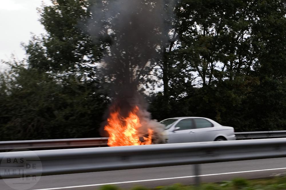 De voorkant van een Alfa staat op de snelweg in licherlaaie