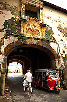 """Galle Fort Old gate is on the Queen Street. The arch on the Fort side of the gate is inscribed with the coat of arms of VOC (Vereenigde Oost Indische Campagnie), showing two lions holding a crest topped by the inevitable cockerel), while the arch on the exterior, port-facing side is decorated with the British crest, """"Dieu et mon droit"""" and the date 1669."""