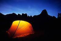 A tent is illuminated at dusk in the Cirque of The Towers.  Wind River Mountains, Wyoming.