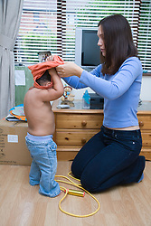 Young mother helping her toddler get dressed,
