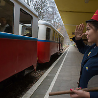 Girl working at the station salutes after signaling the train can leave the station of the Children's Railway in the Buda Hills in Budapest, Hungary on November 13, 2014. ATTILA VOLGYI