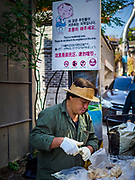 SEOUL, SOUTH KOREA:  A candy vendor in the Bukchon Hanok village in Seoul. Hanok is the traditional style of construction in South Korea and Bukchon is one of the only remaining Hanok communities in Seoul. It is close to Gyeongbokgung Palace and popular with tourists.     PHOTO BY JACK KURTZ
