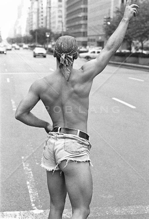 Flamboyant shirtless young man in denim short shorts hailing a cab in NYC, (b&w)