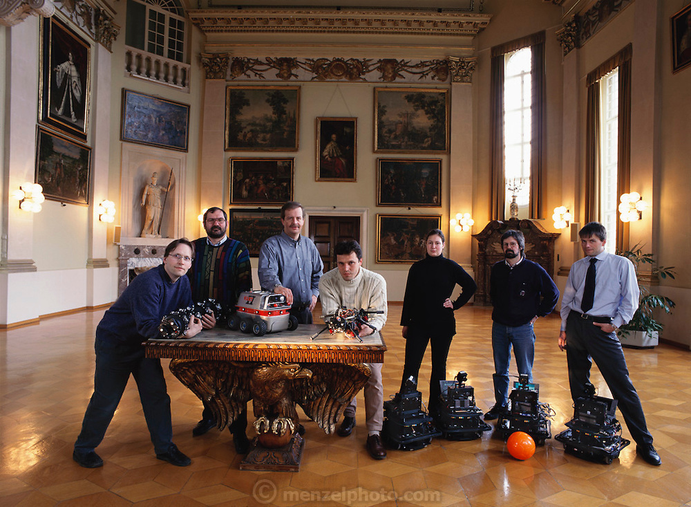"German National Research Center robot scientists pose for a group portrait in the main hall of the center's Schloss Burlinghoven (administrative building of GMD). Left to Right: Bernhard Klaassen holding ""Snake2"", Rainer Worst, Jurgen Vollmer (with hand on KURT, a sewer inspection robot prototype), Frank Kirchner, holding ""Sir Arthur"" a first generation walking robot, Ina Kople, Herman Streich, and Jorg Wilburg. (Three people on right in back of robocup-playing middleweight robots and soccer ball.) Bonn, Germany"