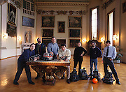 """German National Research Center robot scientists pose for a group portrait in the main hall of the center's Schloss Burlinghoven (administrative building of GMD). Left to Right: Bernhard Klaassen holding """"Snake2"""", Rainer Worst, Jurgen Vollmer (with hand on KURT, a sewer inspection robot prototype), Frank Kirchner, holding """"Sir Arthur"""" a first generation walking robot, Ina Kople, Herman Streich, and Jorg Wilburg. (Three people on right in back of robocup-playing middleweight robots and soccer ball.) Bonn, Germany"""