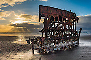 Shipwreck skeleton at sunset. In 1906, the crew of the sailing ship Peter Iredale took refuge at Fort Stevens, after she ran aground on Clatsop Spit. The wreck is visible today, within Fort Stevens State Park, along the Oregon Coast, USA. Active from 1863–1947, Fort Stevens was an American military installation that guarded the mouth of the Columbia River in the state of Oregon. Built near the end of the American Civil War, it was named for a slain Civil War general and former Washington Territory governor, Isaac I. Stevens.