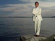 Asian man in suit smiles as he stands in front of a large body of water