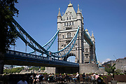 People enjoying a relaxing rest at an outdoor seating space at the base of Tower Bridge in London, England, United Kingdom.