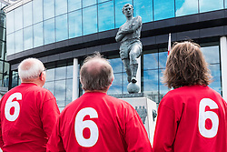 © Licensed to London News Pictures. 30/07/2016. Football fans view the bronze statue of England footballer BOBBY MOORE outside Wembley Stadium on the 50th anniversary of England beating Germany in the World Cup finals on 30th July 1966.  London, UK. Photo credit: Ray Tang/LNP