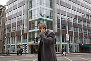 A man uses his mobile phone outside the offices of Cambridge Analytica on New Oxford Street, the UK tech company accused of harvesting the personal details of Facebook users in its data privacy scandal, on 11th April, 2018, in London, England.