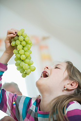 Girl eating bunch of grapes, close up