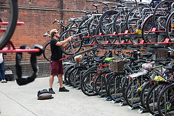 © Licensed to London News Pictures. 06/08/2015. London, UK. A man puts his bicycle in the bike rack at Waterloo station in London. A tube strike today has closed the TfL London Underground network as members of four unions take industrial action for the second time in a month because of a deadlocked dispute over plans to launch a new all-night tube train service next month. Extra busses have been laid on to help commuters get to work. Photo credit : Vickie Flores/LNP