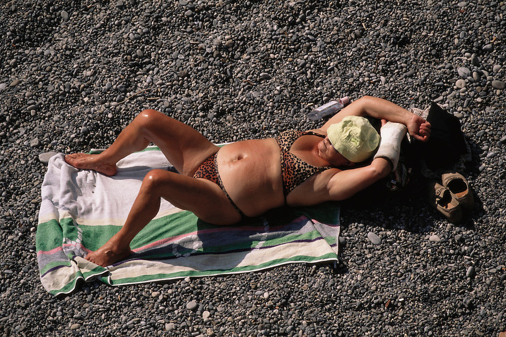 Large elderly woman sunbathes on the rocky beach, Amalfi Coast, Italy.