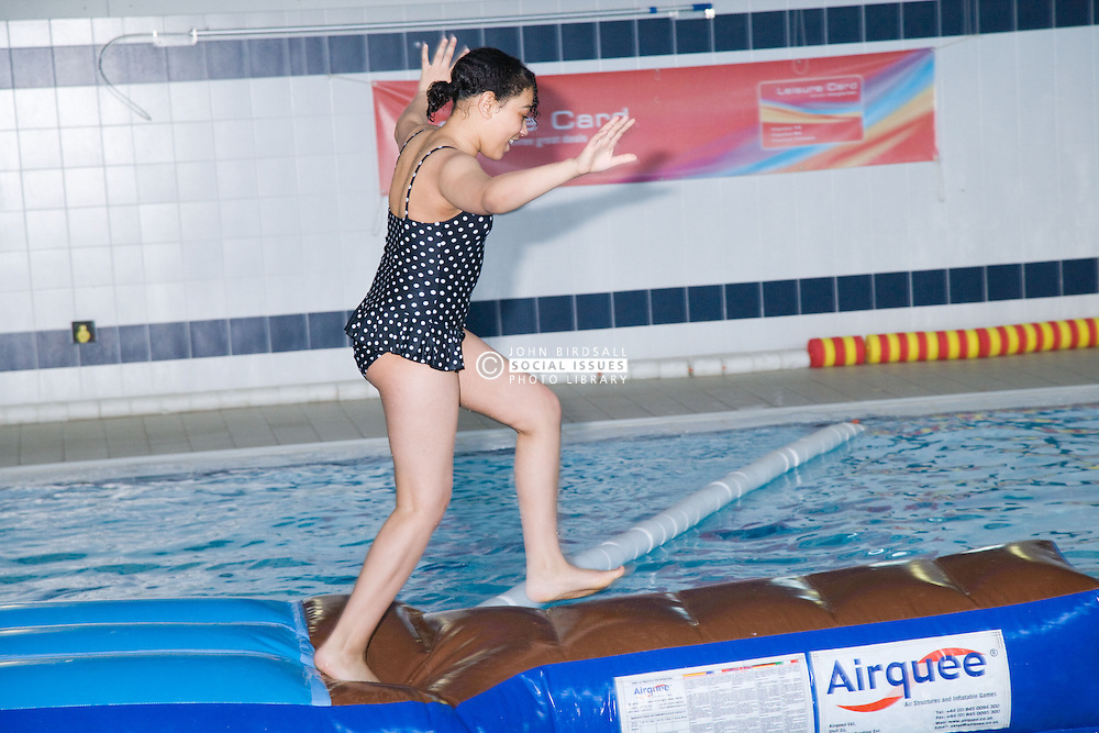 Girl carefully stepping across inflatable floats in the swimming in the pool at her local leisure centre,