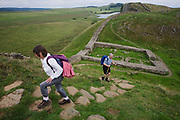Walkers pass near the ruins of Milecastle 39 on Roman Hadrian's Wall, once the northern frontier of Rome's empire from Barbarian tribes. Hadrian's Wall (Latin: Vallum Aelium) was a stone and timber fortification built by the Roman Empire across the width of what is now northern England. Begun in AD 122, during the rule of emperor Hadrian, it was built as a military fortification though gates through the wall served as customs posts to allow trade and levy taxation. The 4.5m high Wall was 80 Roman miles (73.5 miles, 117km) long and so important was it to secure its length that up to 10% of the Roman army total force were stationed here. Tough walkers generally take 7 days to trek its coast-to-coast length.