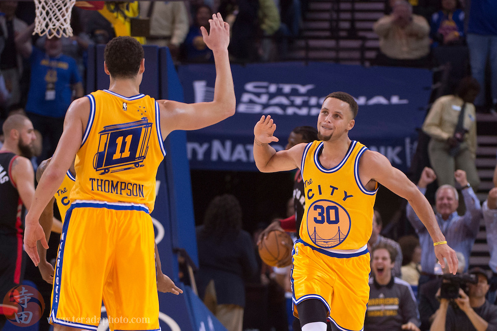 November 17, 2015; Oakland, CA, USA; Golden State Warriors guard Stephen Curry (30) celebrates with guard Klay Thompson (11) during the second quarter against the Toronto Raptors at Oracle Arena.