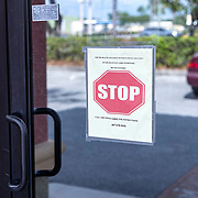 A sign on the front door informs patients who may have flu like symptoms to call the office before entering at Universal Medical Care on Tuesday, March 31, 2020 in Orlando, Florida. Universal Medical Care's on site patient load has been cut by fifty percent and they are currently referring patients with symptoms to local testing sites such as Centra Care or the site at the Orange County Convention Center. (Alex Menendez via AP)