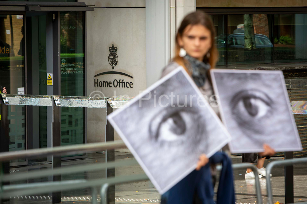 A campaigner holding up watching eyes for a Close Napier Barracks demonstration outside the Home Office headquarters on Marsham street on the 28th September 2021 in London, United Kingdom. Napier Barracks has been used by the Home Office to house Asylum seekers for a year now. Close the Camps organised a solidarity demo for the people in Napier Barracks, there have been numerous calls for the camp to close as the facilities have been deemed unsafe for habitation and unfit for purpose.