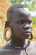 Woman of the Mursi tribe with elongated earlobes, as body ornaments Photographed in Debub Omo Zone, Ethiopia. Close to the Sudanese border.