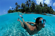 snorkeller in the lagoon of a deserted Maldivian island