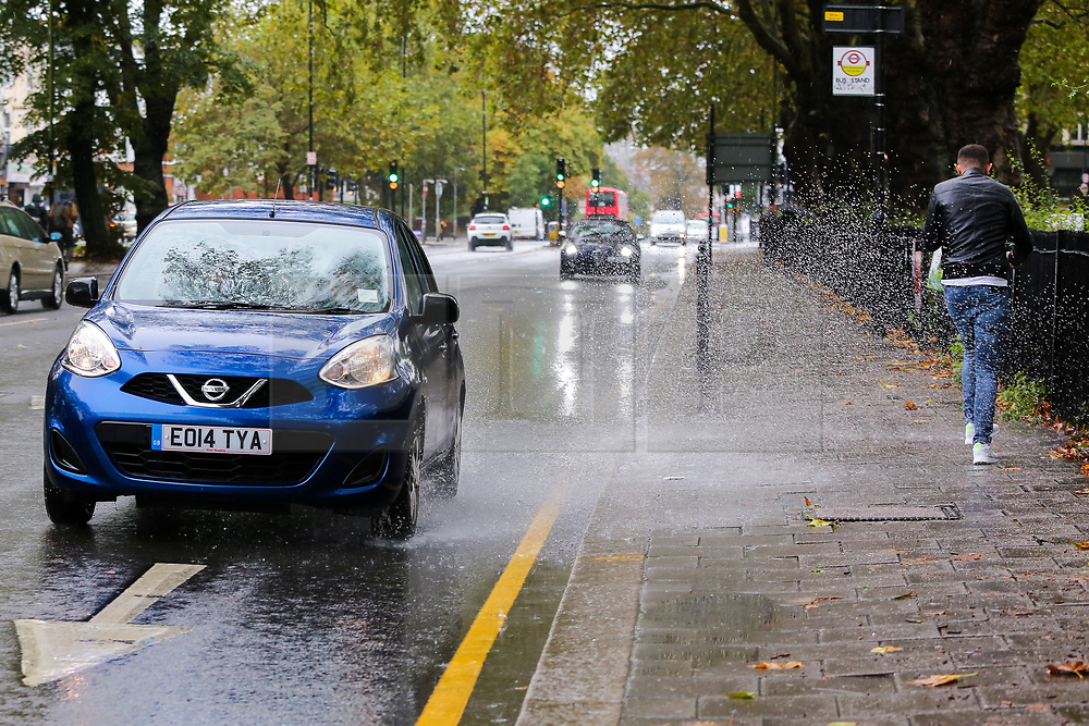© Licensed to London News Pictures. 04/10/2020. London, UK. A man tries to avoid splashing rainwater as a car drives through surface water in north London, as Storm Alex brings heavy rain to large parts of the UK. The Met Office forecasts heavy rain and windy weather for the next of the day in the capital. Photo credit: Dinendra Haria/LNP