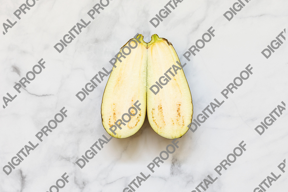 Isolated aubergine sliced at the middle isolated over a white marble background viewed from above - flatlay look