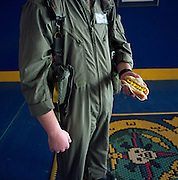 A US Navy airman stands holding a recently-bought hot dog from a food dispenser at the Naval Air Station Sigonella, Sicily Italy. Wearing a green flying suit, the snack is wrapped in a napkin and its chemically-enhanced yellow mustard echoes the stripes and badge of his squadron. Home to over 5,000 military and civilian personnel including family members, Sigonella is an outpost for American nationals who have the luxuries from home freighted out to their remote mission, a hub of naval air operations in the Mediterranean Sea and home comforts keep up morale. Picture from the 'Plane Pictures' project, a celebration of aviation aesthetics and flying culture, 100 years after the Wright brothers first 12 seconds/120 feet powered flight at Kitty Hawk,1903. .