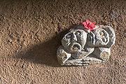 Two sculptured faces on a very rough wall in Bali with a red flower on top and dramatic lighting.